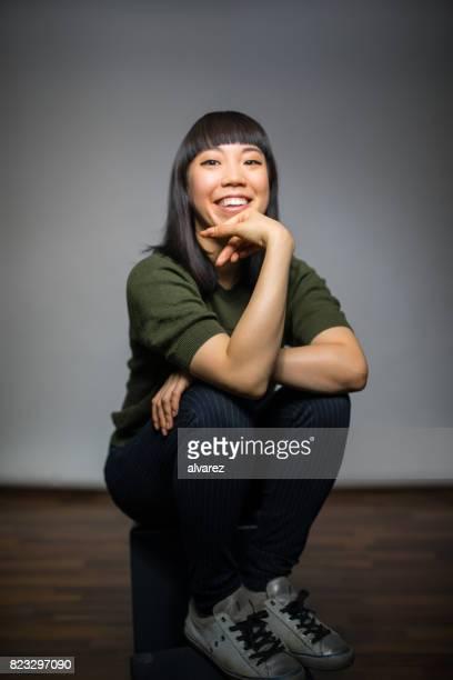 Femme joyeuse assis sur fond gris