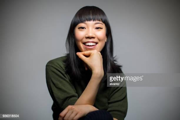 cheerful woman sitting against gray background - retrato formal imagens e fotografias de stock