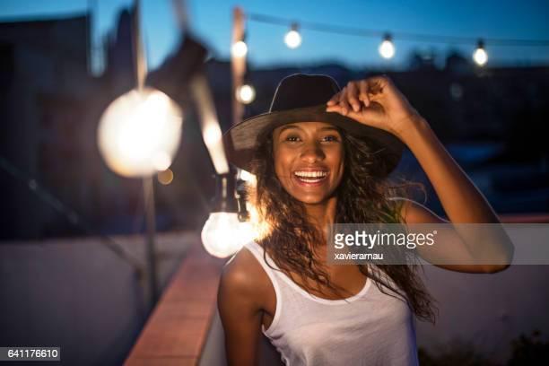 Mujer alegre de pie en terraza iluminada