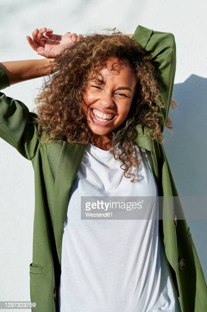 cheerful woman standing with hands behind head during sunny day - green coat stock pictures, royalty-free photos & images