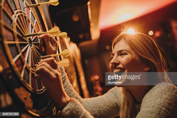 cheerful woman taking darts out of dart board. - dart stock pictures, royalty-free photos & images