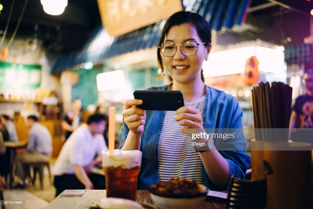 Cheerful woman taking photo of her freshly made meal with mobile phone in a traditional style restaurant