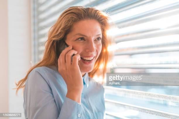 donna allegra che parla sullo smartphone per finestra - slovenia foto e immagini stock