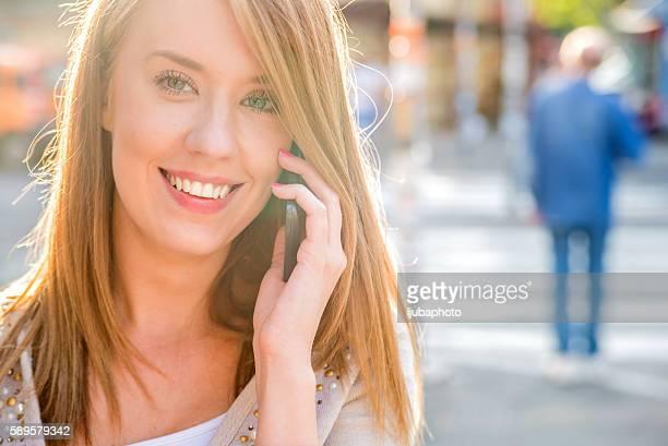 Fröhliche Frau Gespräch am Telefon auf der Straße