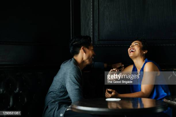 cheerful woman talking to male partner at restaurant - romance stock pictures, royalty-free photos & images
