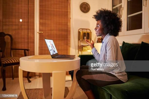 mujer alegre hablando con un amigo por una videollamada durante el coronavirus - antirracismo fotografías e imágenes de stock