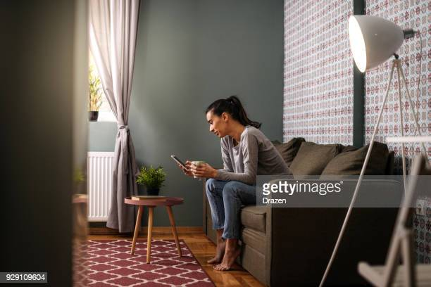Cheerful woman text messaging at home