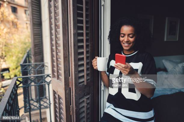 cheerful woman texting at the balcony - online dating stock pictures, royalty-free photos & images