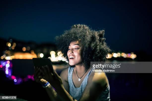 Mujer alegre con tableta digital en la playa por la noche