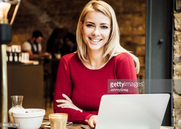 Cheerful woman using laptop in cafe
