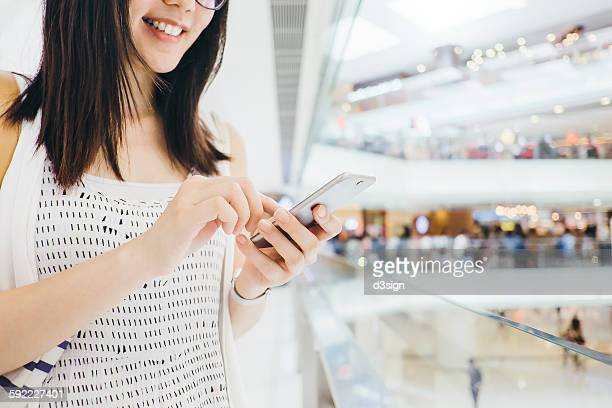 Cheerful woman using smartphone in shopping mall
