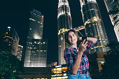 cheerful woman using smartphone outdoor at