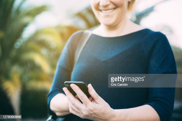 cheerful woman using smartphone outdoors - cris cantón photography fotografías e imágenes de stock