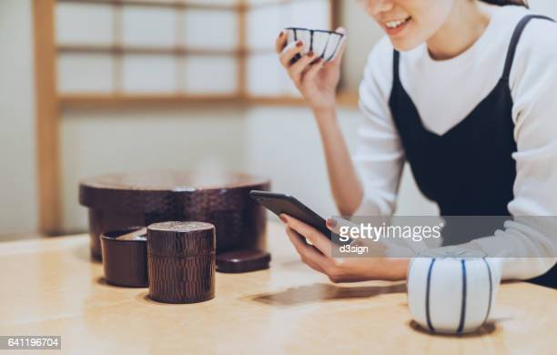 Cheerful woman using smartphone while enjoying cup of tea in traditional Japanese cafe