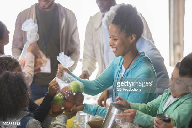 cheerful woman volunteers with children at local food bank - homeless shelter stock pictures, royalty-free photos & images
