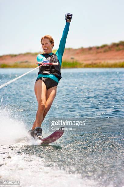 cheerful woman wakeboarding in sea - sport aquatique photos et images de collection