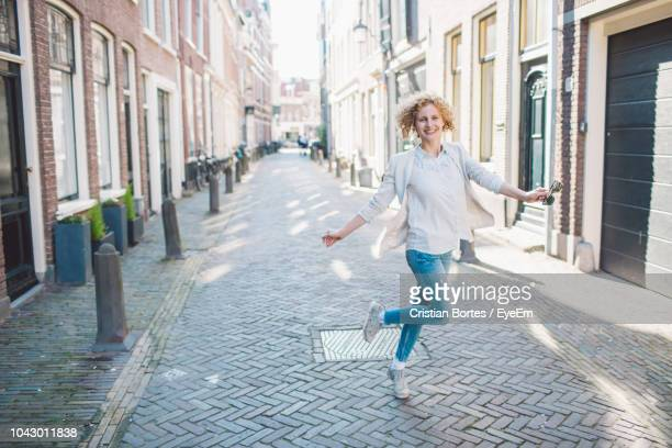 cheerful woman walking on street in city - bortes stock pictures, royalty-free photos & images