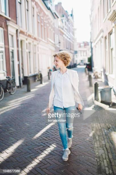 cheerful woman walking on street in city - bortes stockfoto's en -beelden