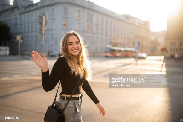 cheerful woman waving at camera as she passes by - greeting stock-fotos und bilder