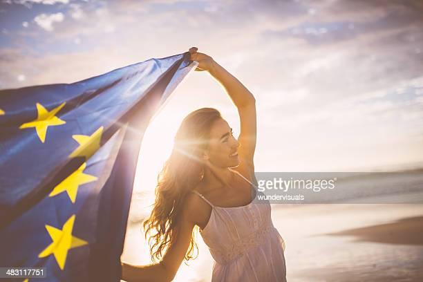 Fröhlich Frau winkt europäische Flagge