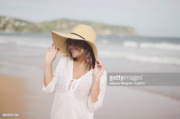 Cheerful Woman Wearing Hat While Standing At Beach