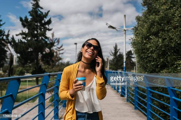 cheerful woman wearing sunglasses talking over smart phone while standing on footbridge in park - ecuador fotografías e imágenes de stock