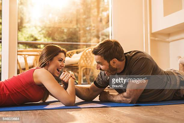 Cheerful woman winning in arm wrestling with her boyfriend.