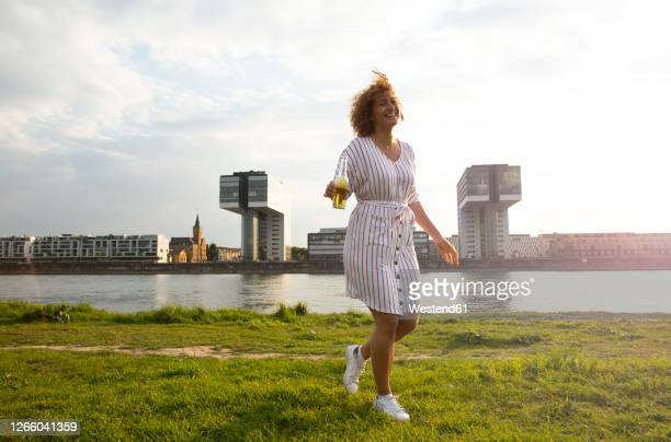 cheerful woman with beer bottle walking on grassy land against river in city at sunset - north rhine westphalia stock pictures, royalty-free photos & images