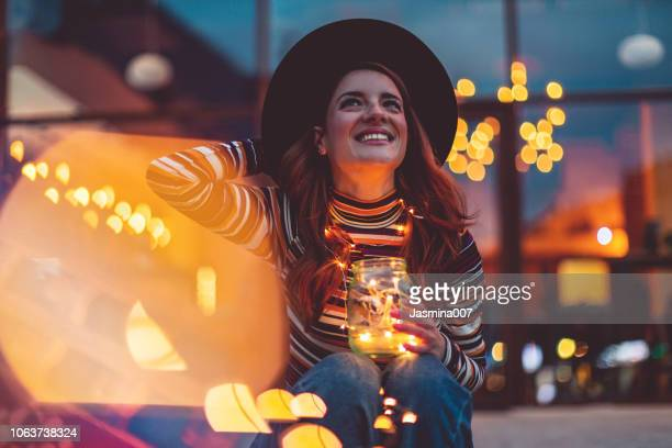 cheerful woman with christmas lights - illuminated stock pictures, royalty-free photos & images