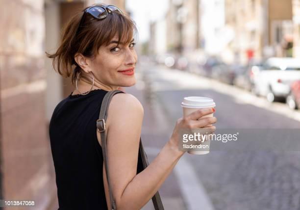 mulher alegre com café na rua olhando para trás - mulheres de idade mediana - fotografias e filmes do acervo
