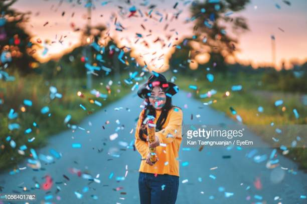 cheerful woman with colorful confetti standing on road during sunset - festeggiamento foto e immagini stock