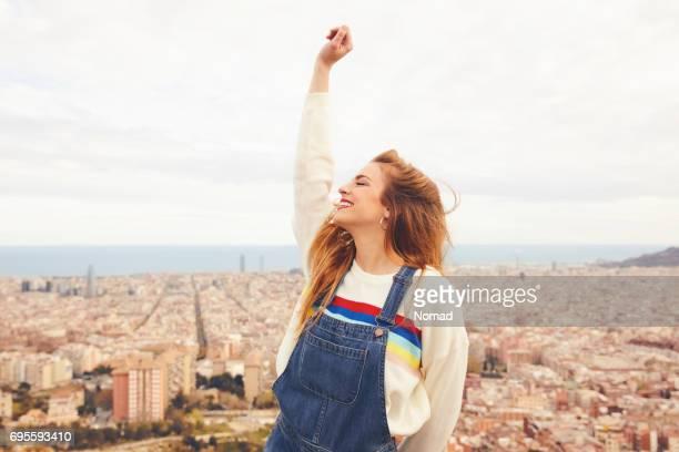 mujer alegre con la mano levantada contra el paisaje urbano - mujeres mano levantada fotografías e imágenes de stock