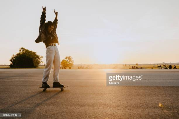 cheerful woman with hand raised skating on road in park - skating stock pictures, royalty-free photos & images