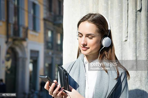 Cheerful Woman With Headphones And Smartphone Enjoying Music