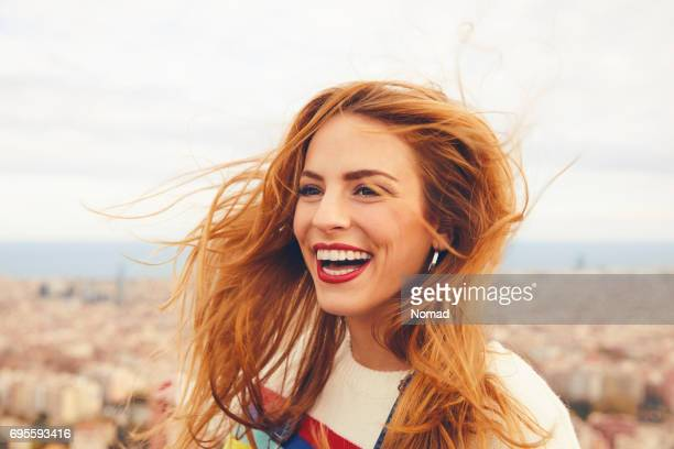 cheerful woman with tousled hair against cityscape - redhead stock pictures, royalty-free photos & images