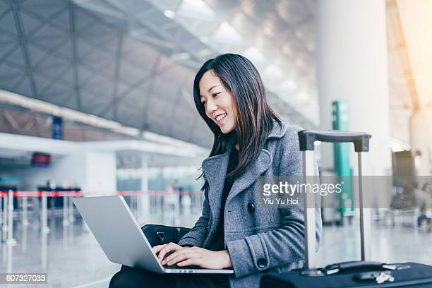 Cheerful woman working on her laptop at airport.