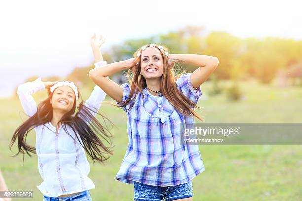 Cheerful women dancing on grassland