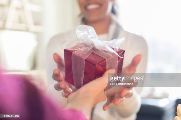 cheerful women exchanging christmas presents - gift stock pictures, royalty-free photos & images