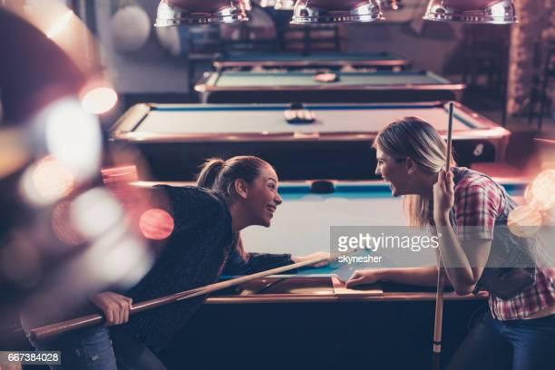 Cheerful women having fun while playing billiard in a pool hall.