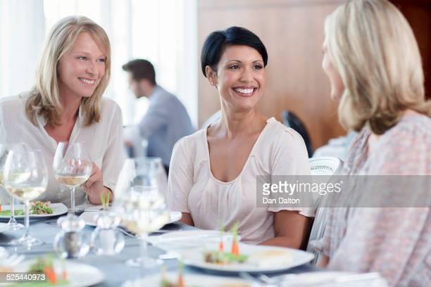 Cheerful women in restaurant, man in background