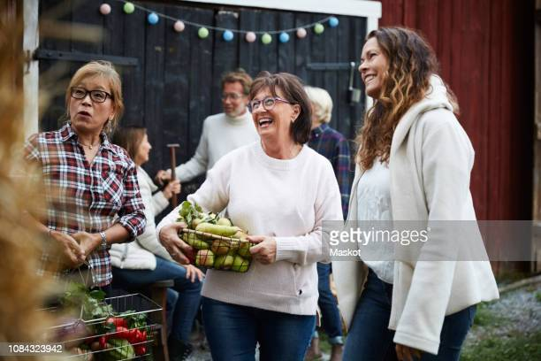 Cheerful women standing with baskets against friends at farm during dinner party
