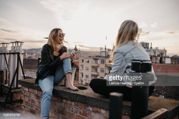 cheerful women talking while sitting on building terrace against sky - building terrace stock pictures, royalty-free photos & images