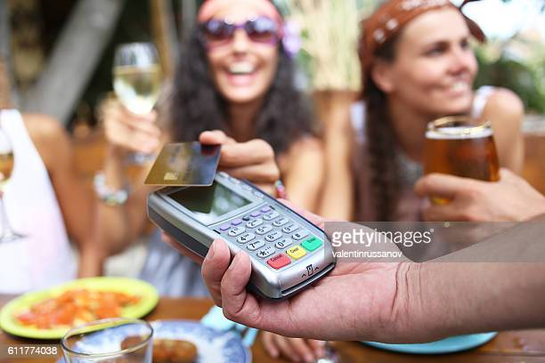 Cheerful women using credit card for contactless payment in bar