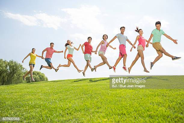 Cheerful young adults jumping on grass