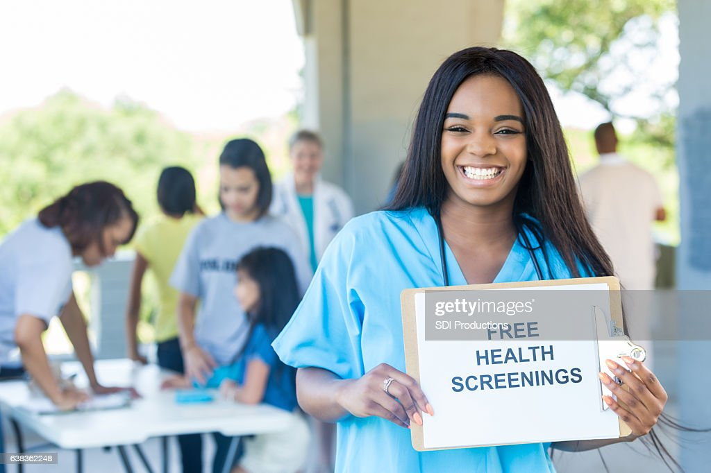 Cheerful young African American nurse promotes health fair : Stock Photo