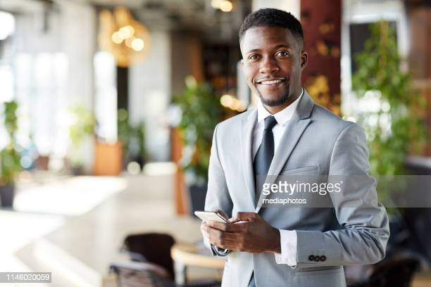 cheerful young african-american businessman with smartphone - businessman stock pictures, royalty-free photos & images