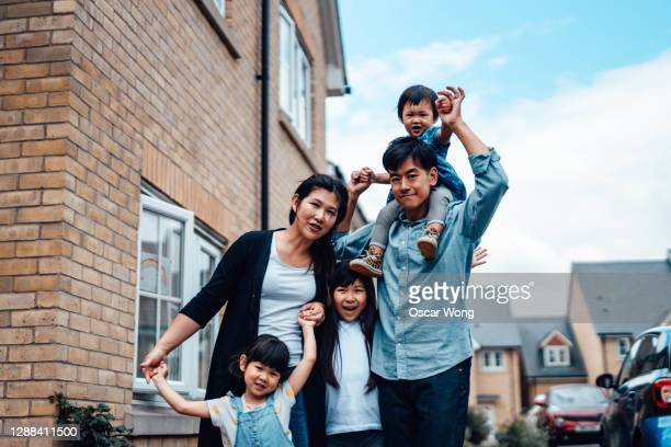 cheerful young asian family standing in front of house - emigration and immigration stock pictures, royalty-free photos & images