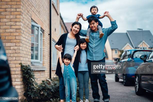 cheerful young asian family standing in front of house - couple stock pictures, royalty-free photos & images