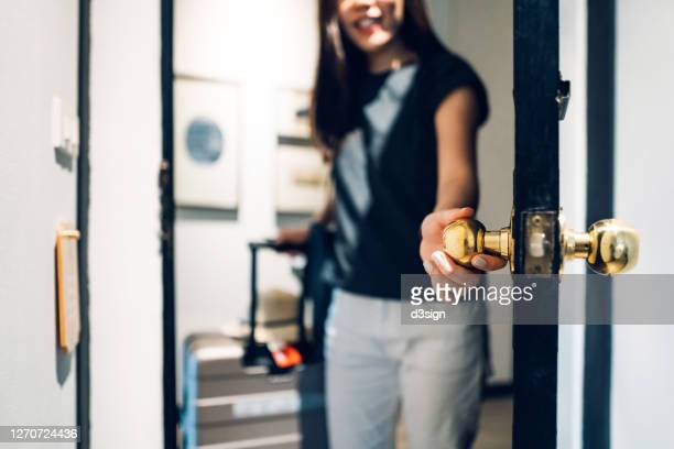 cheerful young asian female traveller opening the door entering the hotel room. she is carrying a suitcase and on vacation - opening event bildbanksfoton och bilder