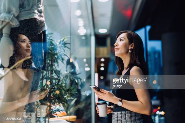 cheerful young asian woman holding a cup of coffee, checking her smartphone while standing outside a boutique looking at shop window in the evening in the city - merchandise stock pictures, royalty-free photos & images
